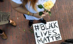 Une femme se tient au dessus d'une pancarte « Black Lives Matter »
