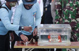 Le personnel de la marine indonésienne manipule une boîte contenant l'enregistreur de données de vol récupéré sur le site de l'accident du vol Sriwijaya Air SJ-182 dans la mer de Java, au port de Tanjung Priok, le 12 janvier 2021.