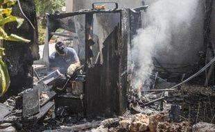 Un expert israélien éteint l'incendie provoqué par la chute d'une roquette palestinienne sur Kfar Aza, le 14 juillet 2014