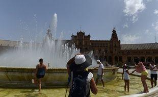 Des promeneurs se rafraîchissent dans une fontaine à Séville, le 1er août 2018.