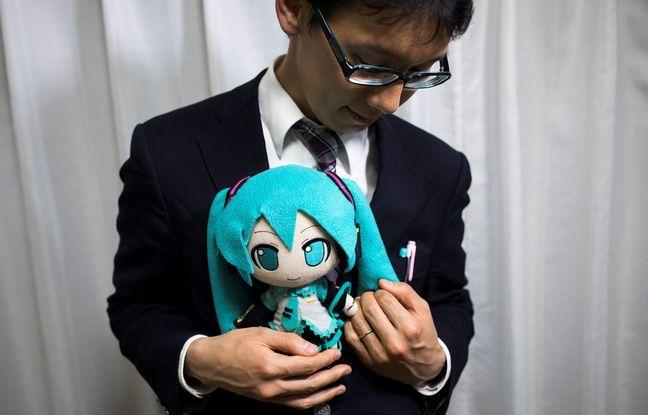 Akihiko Kondo pose avec une poupée du personnage virtuel Hatsune Miku qu'il a épousée.