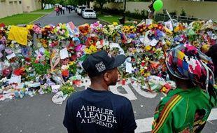 """Un petit autel a été improvisé sur la pelouse, autour de deux palmiers nains. Quelques bougies y brûlent encore. Des fleurs s'amoncellent autour, un tee-shirt à l'effigie de Mandelaa été accroché au jacaranda voisin, sur lequel quelqu'un a écrit: """"Tata Madiba, toujours dans nos coeurs""""."""