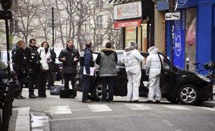 Policiers et enquêteurs examinent le véhicule utilisé par les assaillants qui ont attaqué les locaux du journal satirique Charlie Hebdo faisant au moins 12 morts, le 7 janvier 2014 à Paris