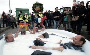 """Des éleveurs français et allemands se baignent symboliquement dans une piscine remplie de lait, le 13 novembre 2015 à Strasbourg, pour signifier qu'ils """"se noient dans les excédents"""""""