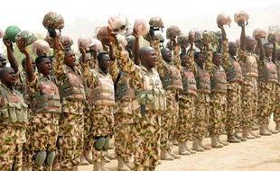 Photo diffusée par le gouvernement nigérian le 26 février 2015 montrant des soldats nigérians engagés dans la lutte contre Boko Haram en train de saluer le président Goodluck Jonathan à son arrivée au village de Mubi, repris aux insurgés