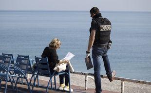 Un policer effectue un contrôle sur la promenade des Anglais, à Nice, dans le cadre du confinement ordonné dans le cadre de la lutte contre la propagation du nouveau coronavirus