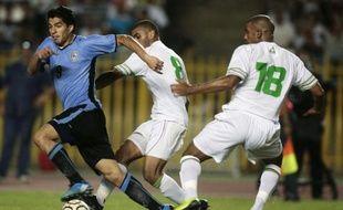 Les Algériens, Lemmouchia Khaled (au centre) et Bouazza Hameur, luttent pour le ballon avec l'Urugayen Luiz Suarez (à gauche), lors d'un match amical, le 13 septembre 2008