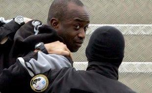 Youssouf Fofana escorté par deux policiers le 4 mars 2005 à l'aéroport d'Abijan