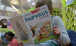 Un enfant lit une BD au salon du livre de Paris.