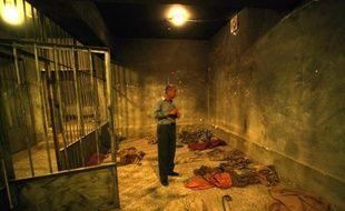 """Kamiran Aziz Ali grimace, les mains dans le dos pour mimer l'instant où en janvier 1990 les sbires de Saddam Hussein l'ont envoyé valdinguer dans une cellule de la """"maison rouge"""", le centre de torture pour militants kurdes à Souleimaniya."""
