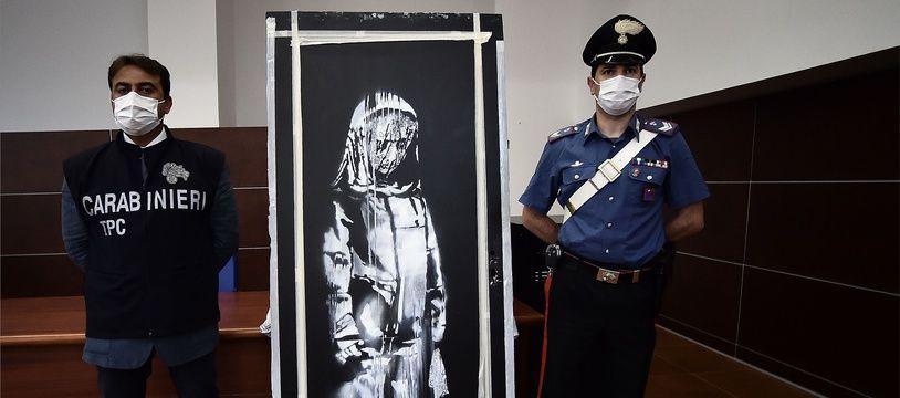 Des carabiniers italiens encadrent l'oeuvre volée attribuée à Banksy.
