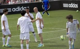 Zinedine Zidane avec ses fils Enzo (à gauche) et Luca (à droite), lors d'un match de foot à Aix-en-Provence, le 23 juin 2011.
