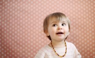 Illustration d'un bébé portant un collier d'ambre, censé soulager les poussées dentaires douloureuses.