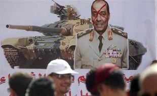 Des manifestants passent devant un portrait barré du maréchal Mohamed Hussein  Tantaoui, le 30 septembre 2011, au Caire.