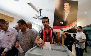 Un Syrien vote le 3 juin 2014 à Damas à l'élection présidentielle, devant une affiche du président sortant Bachar al-Assad, assuré de la victoire