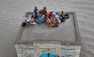 Une famille pakistanaise victime des inondations attend les secours sur le toit d'une mosquée, à Sanawa, dans le Pendjab, le 5 août 2010.