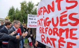 Le ministre de l'Education Vincent Peillon (g) parle le 30 septembre 2013 à Wittenheim avec des personnes manifestant contre la réforme des rythmes scolaires