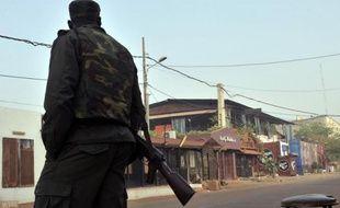 """Un membre des forces de sécurité en poste devant le restaurant """"La terrasse"""" (rideaux bleus) à Bamako le 7 mars 2015"""