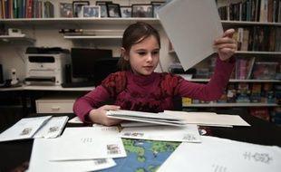 """Morgane, 8 ans, trie le courrier échangé avec """"Rêve aux lettres"""", le 10 novembre 2015 à Strasbourg"""