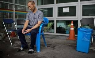 Un homme dont la fille se trouvait à bord du ferry qui a fait naufrage, attend le 7 juillet 2014 devant le gymnase de Jindo