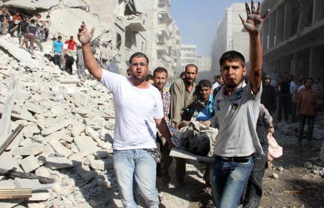Des Syriens évacuent un blessé après un raid aérien sur la ville d'Alep, le 26 août 2013.