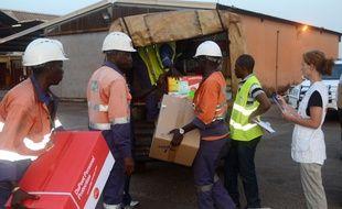 Des travailleurs guinéens chargent du matériel pour l'ONG Médecins sans frontières à l'aéroport de Conakry, le 29 mars 2014.