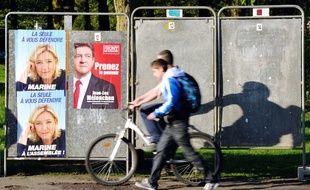 Hénin-Beaumont, le 25 mai 2012. Deux jeunes passent devant des affiches de Marine Le Pen placardées avant les élections législatives de 2012.