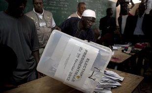 Le responsable d'un bureau de vote vide une urne à Dakar (Sénégal), le 26 février 2012.