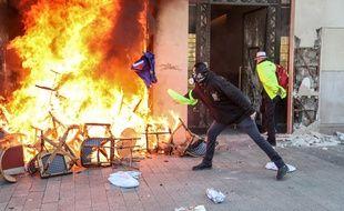 Paris, le 16 mars 2019. Un manifestant jette un drapeau européen dans un brasier allumé devant un magasin situé sur les Champs-Elysées.