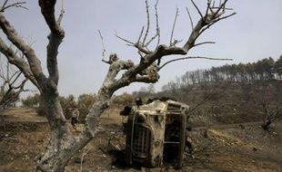 Un véhicule des pompiers carbonisés vers le village de Artemida en Grèce
