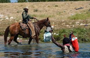 Un agent de la patrouille frontalière des Etats-Unis à cheval tente d'empêcher un migrant haïtien d'entrer dans un campement sur les rives du Rio Grande près du pont international Acuna Del Rio, à Del Rio, Texas, le 19 septembre 2021.