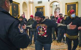 Trump supporters gesture to U.S. Capitol Police in the hallway outside of the Senate chamber at the Capitol in Washington, Wednesday, Jan. 6, 2021. (AP Photo/Manuel Balce Ceneta)/DCMC310/21006779971682//2101062244