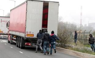 Des migrants tentant de pénétrer dans un camion près de Calais en octobre 2014