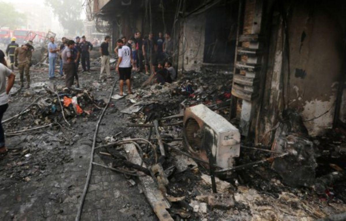 Bagdad (Irak), le 3 juillet. Des Irakiens inspectent les décombres après un attentat qui a fait au moins 213 morts le 2 juillet sur un marché de Bagdad. – SABAH ARAR / AFP