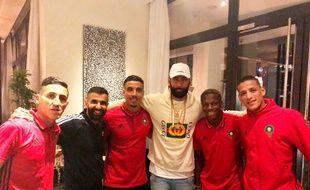 La Fouine entouré de joueurs de l'équipe du Maroc.