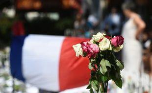 Des roses fanées posées près d'un drapeau national français, le 16 juillet 2016 sur la Promenade des Anglais à Nice