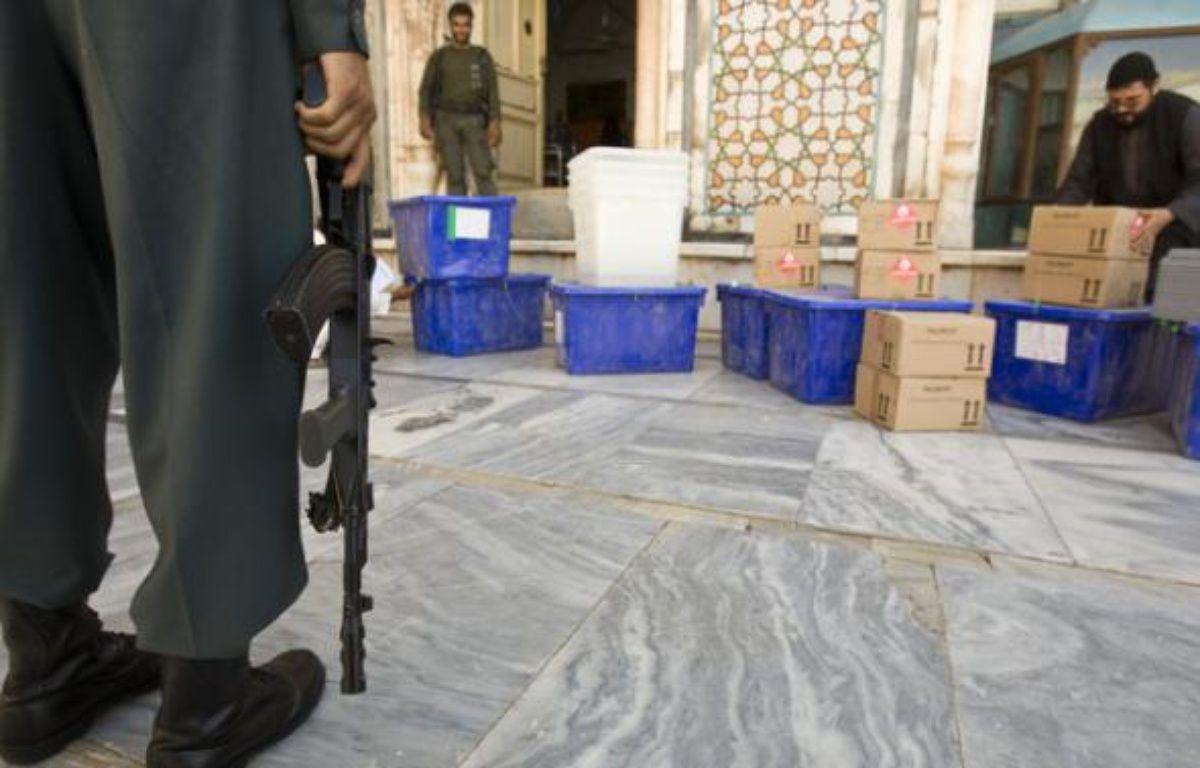 Un policier afghan tient la garde devant du matériel de vote à Herat, Afghanistan.  – REUTERS/Raheb Homavandi