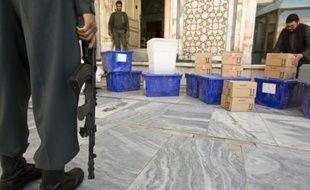 Un policier afghan tient la garde devant du matériel de vote à Herat, Afghanistan.