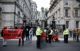 Des policiers se tiennent près d'une statue de Boris Johnson recouverte de pétrole par des militants de Greenpeace sur Whitehall devant les portes de Downing Street, à Londres, Royaume-Uni, le 11 octobre 2021.