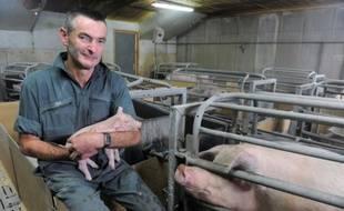 L'agriculteur français Jean-Michel Juhel pose avec un porcelet dans les bras dans sa ferme de Plédéliac, dans l'ouest de la France le 20 juillet 2015