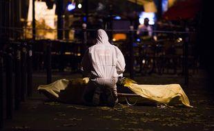 Un médecin légiste travaillent dans la rue après l'attentat terroriste, le 13 novembre 2015, à Paris.