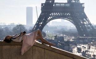 Une touriste prend le soleil le 14 février dans les jardins du Trocadéro à Paris.