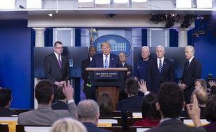 Le président américain Donald Trump, avec des membres du groupe de travail sur le coronavirus,  dans la salle de presse Brady de la Maison Blanche à Washington, le 21 mars 2020.