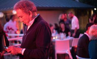 Michel Drucker consulte son smartphone lors du festival Des livres des stars à Marseille, en juin 2018.