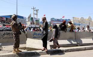 Des talibans surveillent les alentours de l'aéroport de Kaboul, où des familles tentent de monter dans un avion à Kaboul.