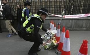 Une policière anglaise dépose des fleurs en mémoire des victimes des attaques de mercredi.