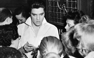 Elvis Presley  signe des autographes à des fans après un concert, en 1958.