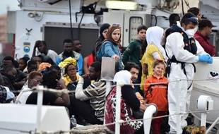"""Des migrants attendent pour débarquer du navire """"Fiorillo"""" des garde-côtes italiens dans le port de Palerme, le 20 octobre 2014, après une opération Mare Nostrum de sauvetage en mer"""