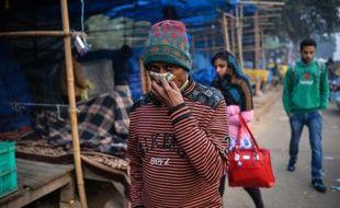 Un passant tente  de se protéger de la pollution le 18 décembre 2015 dans le quartier d'Anand Vihar à New Delhi