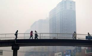 Des habitants de Shenyang sur un pont piétonnier, lors d'un jour de pollution en 2015 (photo d'illustration)